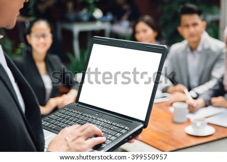 portrait of businessman doing presentation with laptop in front of his team while having a coffee break at cafe - stock photo