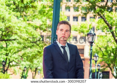 Portrait of Businessman. Dressing in dark blue suit, black tie, a young guy standing against light pole on street in New York, looking up, thinking. Concept of business and environment protection. - stock photo