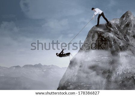Portrait of businessman help his partner to climb the cliff by pulling her with a rope - stock photo