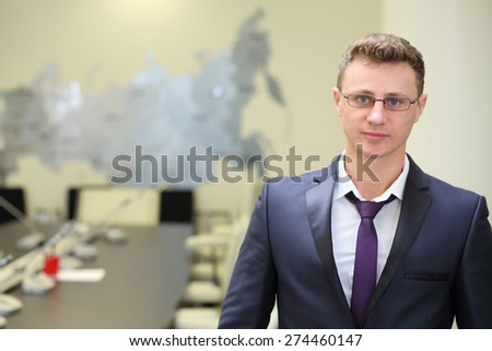 Portrait of businessman in glasses in conference room with map of Russia - stock photo