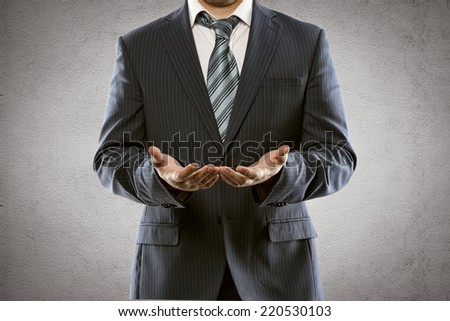 Portrait of businessman in luxury suit and tie offering smth in his hands. Young man standing with open palms posing in studio.  - stock photo