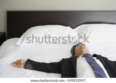 Portrait of businessman laying on bed - stock photo