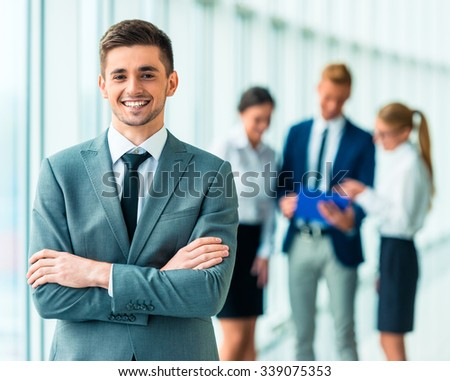 Portrait of businessman on the background of their colleagues in the office - stock photo