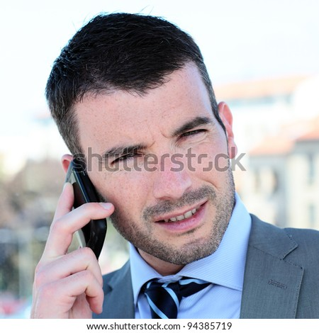 portrait of businessman on the phone outdoor - stock photo