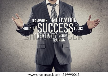 Portrait of businessman showing business elements of success. Young man wearing business suit standing with open arms in studio.   - stock photo