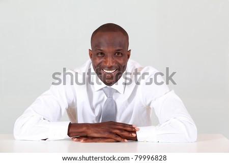 Portrait of businessman sitting at his desk - stock photo
