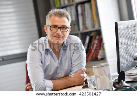 Portrait of businessman sitting in office - stock photo
