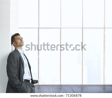 Portrait of businessman standing in empty office lobby, thinking, looking up. Copyspace.? - stock photo