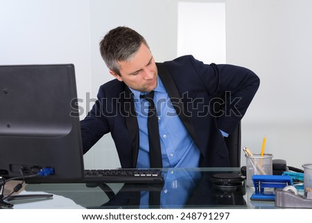 Portrait Of Businessman Suffering From Backpain In Office - stock photo