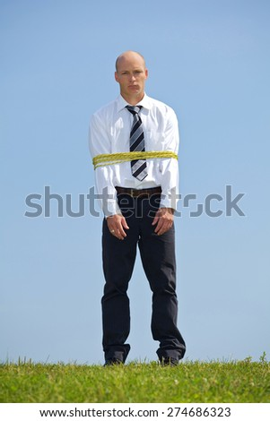 Portrait of businessman tied up with ropes in park - stock photo