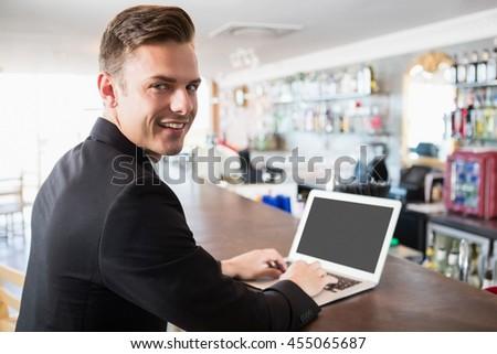 Portrait of businessman using laptop in restaurant - stock photo