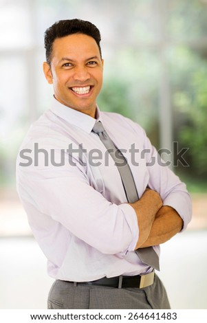 portrait of businessman with arms crossed in modern office - stock photo