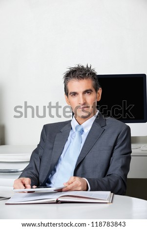 Portrait of businessman with digital tablet sitting at desk in office - stock photo