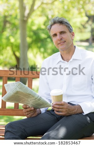 Portrait of businessman with disposable cup and newspaper in the park - stock photo