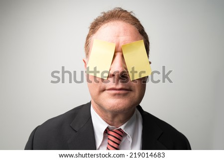 Portrait of businessman with his eyes covered by yellow stickers - stock photo