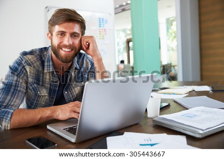 Portrait Of Businessman Working In Creative Office - stock photo