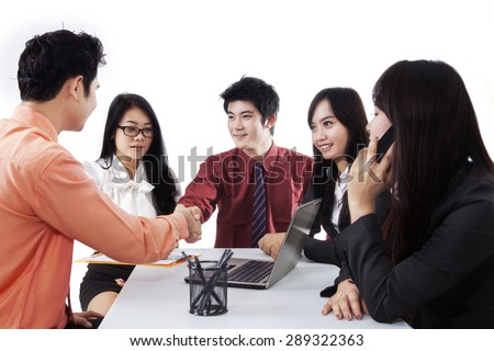Portrait of businessmen agree to cooperate and symbolized by shaking hands in a meeting - stock photo