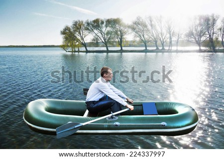 Portrait of businessmen sailing on rubber boat along island with summer trees with green leaves against sun light and sky with clouds background Alone business man with paddle Concept Idea  - stock photo