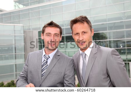 Portrait of businessmen standing in front of modern building - stock photo