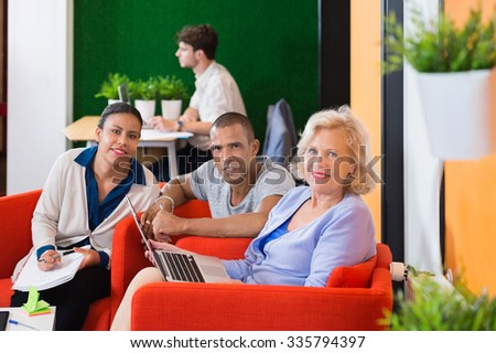 Portrait of businesspeople discussing plan while sitting at modern office lobby - stock photo