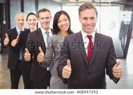 Portrait of businesspeople giving thumbs up in office - stock photo