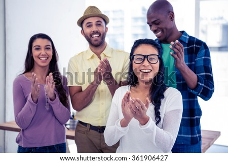 Portrait of businesswoman applauding with team in creative office - stock photo