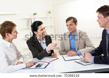 Portrait of businesswoman explaining work to his colleagues in office - stock photo
