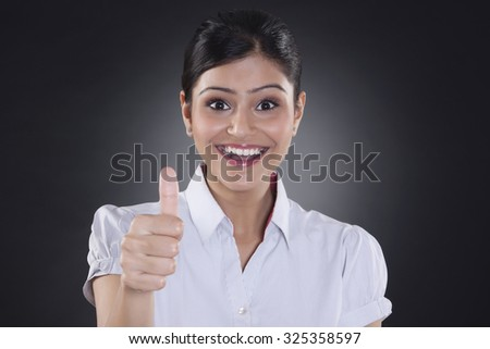 Portrait of businesswoman giving thumbs up - stock photo