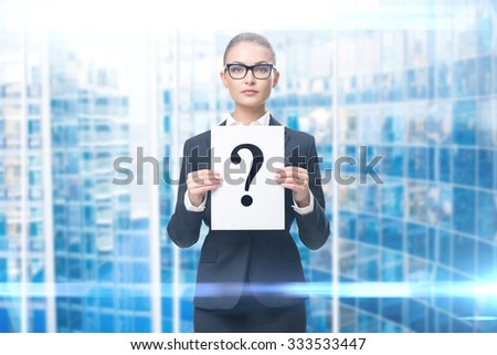 Portrait of businesswoman handing question mark, blue background. Concept of problem and solution - stock photo
