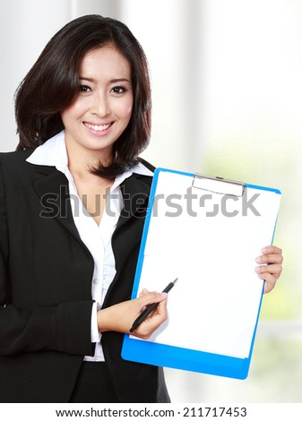 portrait of businesswoman showing a blank paper - stock photo