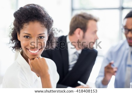 Portrait of businesswoman sitting with hand on chin in office while colleagues discussing in background - stock photo