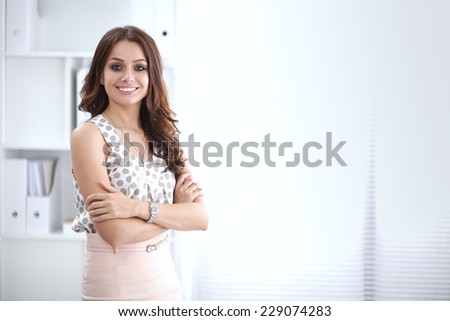 Portrait of businesswoman standing with crossed arms in office - stock photo