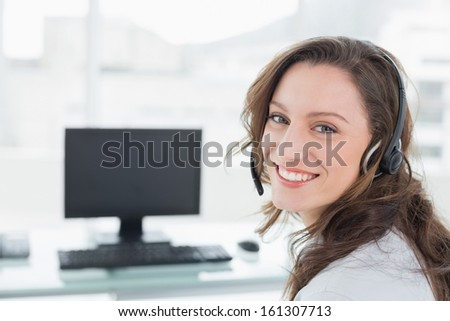 Portrait of businesswoman wearing headset in front of computer in a bright office - stock photo