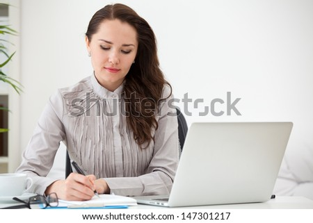 Portrait of businesswoman with laptop writes on a document at office - stock photo