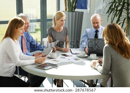 Portrait of businesswomen and businessmen sitting around conference table and consulting. Business people working with digital tablet and laptop.  - stock photo