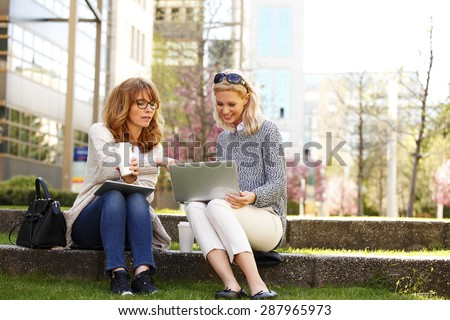 Portrait of businesswomen sitting at office park while using digital tablet and laptop. Business team working online togetherness while consulting.  - stock photo