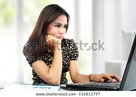 Portrait of busy business woman working at her office - stock photo