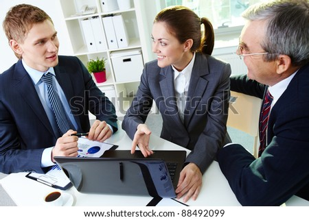 Portrait of busy people discussing new project at meeting in office - stock photo