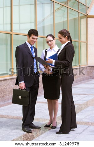 Portrait of busy people discussing new project or working plan outdoors - stock photo