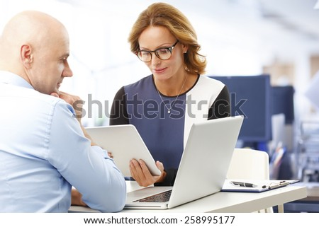 Portrait of busy sales team working on project while sitting at desk in front of computer and digital tablet. Teamwork.  - stock photo