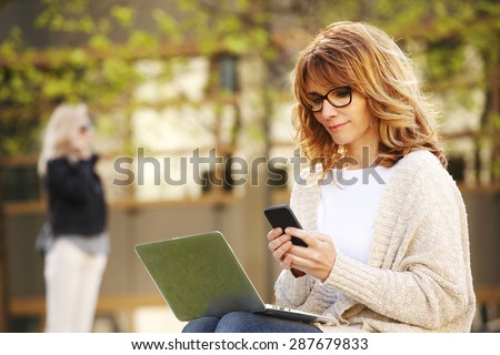 Portrait of busy sales woman sitting at business park and using her laptop while writing text on mobile. Businesswoman working online.  - stock photo