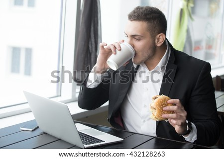 Portrait of busy young business man sitting with glass of drink and hamburger in fast food restaurant interior. Attractive caucasian man eating and using notebook computer in cafe. Indoors - stock photo