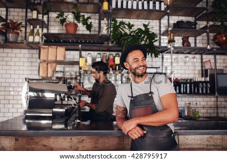 Portrait of cafe owner wearing a hat and apron standing at the counter and looking away. Barista working in background behind the counter making drinks. - stock photo