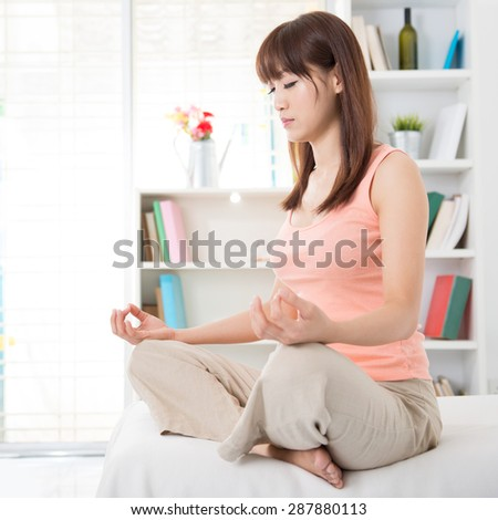 Portrait of calm Asian girl meditation in the morning. Young woman indoors living lifestyle at home. - stock photo
