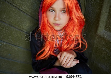 Portrait of calm Halloween girl with red hair looking at camera - stock photo