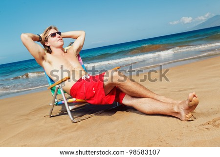 Portrait of calm young man relaxing on the beach - stock photo