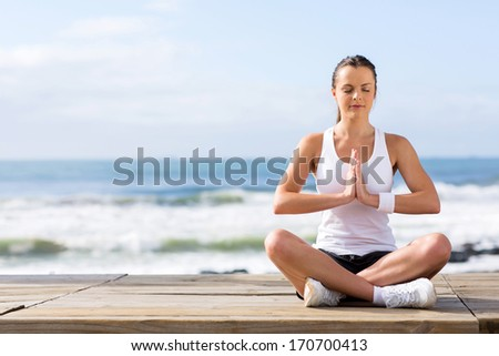 portrait of calm young woman meditating at the beach - stock photo