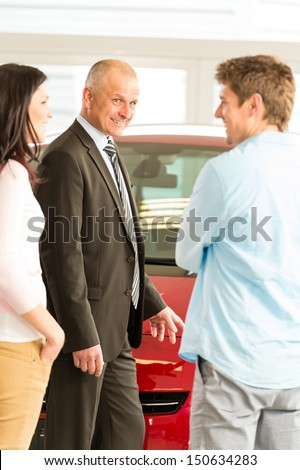 Portrait of car dealer talking with customers - stock photo