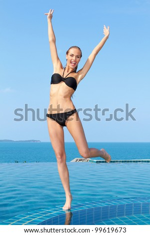 Portrait of carefree woman having fun with arms outstretched at the pool - stock photo