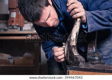 Portrait of Carpenter restoring Wooden Furniture with sandpaper in his workshop. - stock photo